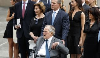 FILE - In this April 21, 2018, file photo, former President George H.W. Bush, in wheelchair, his son former President George W. Bush, and other family members watch as the casket of former first lady Barbara Bush is loaded into a hearse at St. Martin's Episcopal Church in Houston. Former President George H.W. Bush, hospitalized the day after his wife's funeral, will remain hospitalized at least another day a family spokesman said, Wednesday, May 2, 2018. He's being treated for an infection that spread to his blood. (AP Photo/Evan Vucci, File)