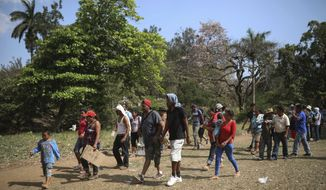 "FILE - In this April 2, 2018 file photo, Central American migrants arrive to a sports center during the annual Migrant Stations of the Cross caravan, or ""Via crucis,"" organized by the ""Pueblo Sin Fronteras"" activist group, in Matias Romero, Oaxaca state, Mexico. The group that led a monthlong caravan of Central Americans seeking asylum in the United States wanted to draw attention to the plight of people in the violent region. (AP Photo/Felix Marquez, File)"