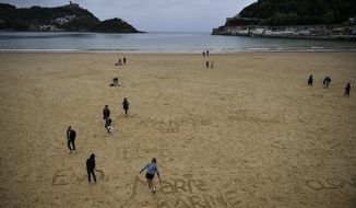 People walk along the sand at La Concha beach, in the Basque city of San Sebastian, northern Spain, Wednesday, May 2, 2018. (Alvaro Barrientos)