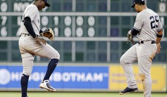 New York Yankees' shortstop Didi Gregorius (18) and second baseman Gleyber Torres (25) do a victory dance at second base after their 6-5 win over the Houston Astros in a baseball game Thursday, May 3, 2018, in Houston. (AP Photo/Michael Wyke)
