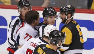 Officials separate Washington Capitals' T.J. Oshie (77) and Pittsburgh Penguins' Kris Letang (58) after a fight late in the third period in Game 4 of an NHL second-round hockey playoff series in Pittsburgh, Thursday, May 3, 2018. The Penguins won 3-1. (AP Photo/Gene J. Puskar) ** FILE **