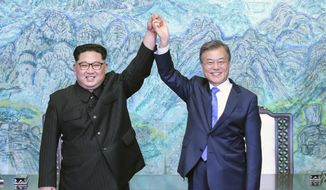 This April 27, 2018, file photo shows North Korean leader Kim Jong-un, left, and South Korean President Moon Jae-in raising their hands after signing a joint statement at the border village of Panmunjom in the Demilitarized Zone, South Korea. (Korea Summit Press Pool via AP, File)