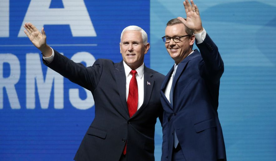 Vice President Mike Pence and Chris Cox, executive director of the National Rifle Association-Institute for Legislative Action wave from the stage at the Leadership Forum in Dallas, Friday, May 4, 2018. (AP Photo/Sue Ogrocki)