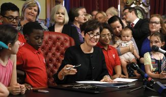Iowa Gov. Kim Reynolds, center, signs a six-week abortion ban bill into law during a ceremony in her formal office, Friday, May 4, 2018, in Des Moines, Iowa. The bill gives Iowa the strictest abortion restrictions in the nation, setting the state up for a lengthy court challenge. (AP Photo/Charlie Neibergall)