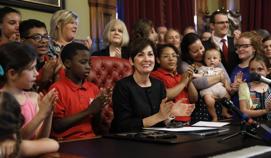 Iowa Gov. Kim Reynolds, center, reacts after signing a six-week abortion ban bill into law during a ceremony in her formal office, Friday, May 4, 2018, in Des Moines, Iowa. The bill gives Iowa the strictest abortion restrictions in the nation, setting the state up for a lengthy court challenge. (AP Photo/Charlie Neibergall) ** FILE **