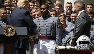 FILE - In this May 1, 2018 file photo, Army head football coach Jeff Monken, right, looks on as President Donald Trump shakes hands with quarterback Ahmad Bradshaw during a ceremony to present the Commander in Chief trophy to the U.S. Military Academy football team in the Rose Garden of the White House in Washington. (AP Photo/Evan Vucci, File)