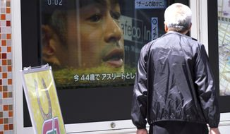 "A pedestrian watches a TV news reporting on Seattle Mariners outfielder Ichiro Suzuki, in Tokyo Friday, May 4, 2018. Suzuki has not officially retired, but his move to the front office of the Seattle Mariners is seen by many in Japan as the beginning of a long ""Sayonara"" for a national treasure. (AP Photo/Eugene Hoshiko)"