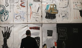 FILE- In this April 9, 2018 file photo, a man looks at the painting entitled 'Flesh and Spirit' by Jean-Michel Basquiat, in London, Prominent art collector Hubert Neumann has filed a lawsuit against Sotheby's auction house on Thursday, May 3, 2018, seeking to block the artist's daughter from selling the masterpiece that's worth an estimated $30 million. (AP Photo/Frank Augstein, File)