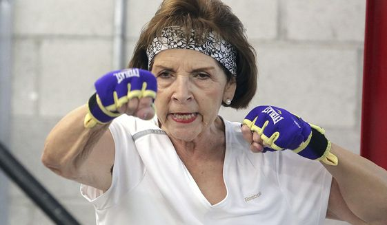 Carson City resident Gloria Navarro warms up with a jabbing drill at the beginning of the hour long Parkinson's boxing program. Navarro, living with Parkinson's and still working a full time job at the Attorney General's office poses its own sorts of challenges, but she manages for the love of her career.  (Jim Grant /Nevada Appeal via AP)