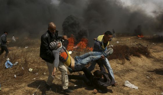 """File - In this Friday, April 27, 2018 file photo, Palestinian protesters evacuate a wounded youth during a protest at the Gaza Strip's border with Israel, east of Khan Younis. The deadly scenes that have been playing out for weeks now along Gaza's border, with thousands of Palestinians marching and threatening to storm the security fence and Israeli troops opening fire, are eerily familiar to Israeli author Mishka Ben-David. They have already taken place _ on the pages of his best-selling thriller last year, """"The Shark."""" And while the novel's doomsday scenario may seem far-fetched to some, Ben-David fears for the region in the absence of an overall peace initiative. (AP Photo/Adel Hana, File)"""