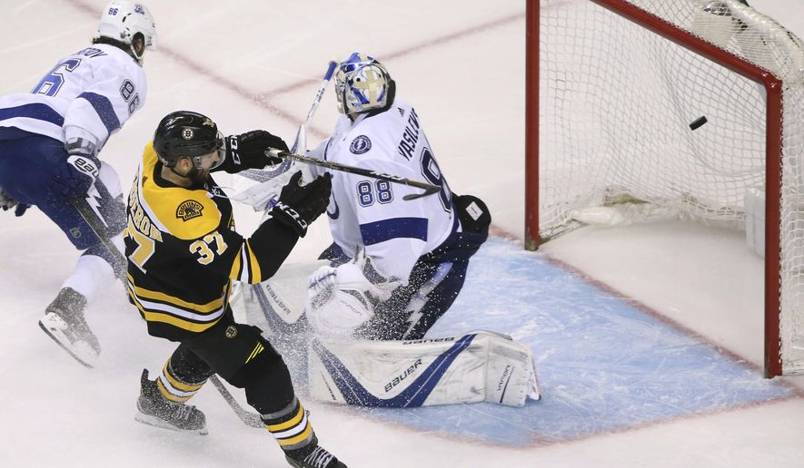 Boston Bruins center Patrice Bergeron (37) scores against Tampa Bay Lightning goaltender Andrei Vasilevskiy (88) as Lightning right wing Nikita Kucherov (86) defends during the third period of Game 4 of an NHL hockey second-round playoff series Friday, May 4, 2018, in Boston. (AP Photo/Elise Amendola)
