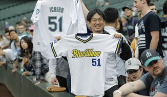 Fans hold Ichiro Suzuki jerseys from the Seattle Mariners and Orix BlueWave before  a baseball game between the Mariners and the Oakland Athletics, Thursday, May 3, 2018, in Seattle. Suzuki was released Thursday by the Mariners and is shifting into a front office role with the team. (AP Photo/Ted S. Warren)