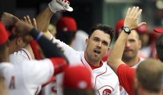 Cincinnati Reds' Adam Duvall celebrates with teammates after hitting a solo home run in the first inning of a baseball game against the Miami Marlins, Friday, May 4, 2018, in Cincinnati. (AP Photo/Aaron Doster)