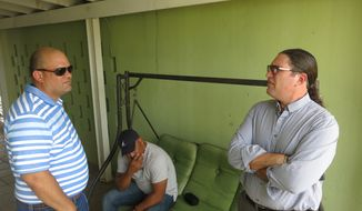 Juan Polanco, left, Denis Oliveras, center, and Carlos Narvaez, all childhood friends of deceased military pilot Maj. Jose Rafael Roman, gather at Roman's family home in Manati, Puerto Rico, Thursday, May 3, 2018. Military investigators began the arduous task Thursday of answering why a C-130 Hercules cargo plane being flown into retirement by an experienced crew of nine airmen plunged onto a Georgia highway. Families and friends grieved and took note of the fact that Puerto Rico's planes are the oldest in the National Guard inventory. The men said that Roman always dreamt of being a pilot and that they would sometimes joke about how old the planes were that he flew. (AP Photo/Danica Coto)