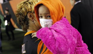 FILE - In this Thursday, Nov. 6, 2014, file photo Leah Still is carried off the field by her grandmother following a ceremony during the first half of an NFL football game between the Cincinnati Bengals and the Cleveland Browns in Cincinnati. Devon Still retired from football and started his second career, trying to help families cope with childhood cancer. He's using lessons learned through his experience with 7-year-old daughter Leah, who became a national story during her recovery from the disease. (AP Photo/AJ Mast, File)