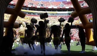 FILE - In this Aug. 24, 2013, file photo, Washington Redskins cheerleaders run out of a tunnel before an NFL preseason football game against the Buffalo Bills in Landover, Md. The Redskins say they're concerned by allegations made by cheerleaders in a New York Times article about a trip to Costa Rica for a photo shoot in 2013. Team president Bruce Allen said in a statement Thursday, May 3, 2018, that the organization is immediately looking into the situation. (AP Photo/Patrick Semansky, File)