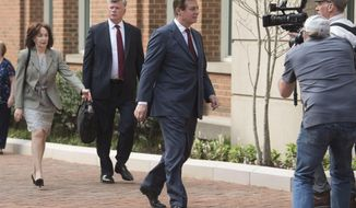 Paul Manafort walks into the Alexandria Federal Courthouse on Friday, May 4, 2018, in Alexandria, Va., with his wife Kathleen Manafort, left, and Kevin Downing, attorney for Manafort. (AP Photo/Kevin Wolf)