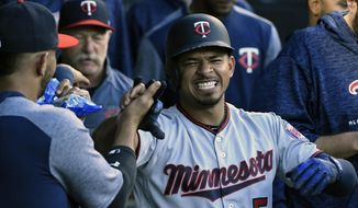 Minnesota Twins' Eduardo Escobar (5) is greeted in the dugout after hitting a home run against the Chicago White Sox during the second inning of a baseball game, Friday, May 4, 2018, in Chicago. (AP Photo/David Banks)
