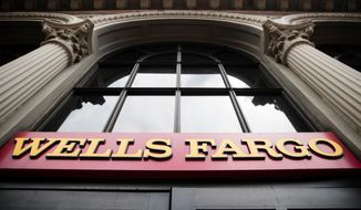 FILE- This Friday, Aug. 11, 2017, file photo shows a sign at a Wells Fargo bank location in Philadelphia. Wells Fargo says it has agreed to pay $480 million to resolve a class-action lawsuit brought by shareholders who claim the bank misstated or failed to disclose details about its sales practices. The San Francisco-based bank said Friday, May 4, 2018, that the agreement is in principle, and must be approved by the court before it's finalized. (AP Photo/Matt Rourke, File)