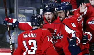Washington Capitals left wing Jakub Vrana (13), from the Czech Republic, center Evgeny Kuznetsov (92), from Russia, and left wing Alex Ovechkin (8), also from Russia, celebrate Kuznetsov's goal during the third period of Game 5 in the second round of the NHL Stanley Cup hockey playoffs against the Pittsburgh Penguins, Saturday, May 5, 2018, in Washington. (AP Photo/Alex Brandon)