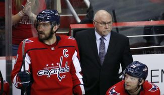 Washington Capitals left wing Alex Ovechkin (8), from Russia, and head coach Barry Trotz stand in the bench during the third period of Game 5 in the second round of the NHL Stanley Cup hockey playoffs, Saturday, May 5, 2018, in Washington. The Capitals won 6-3. (AP Photo/Alex Brandon) ** FILE **