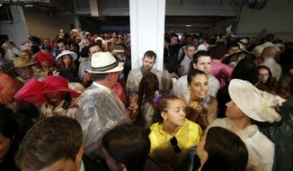 Fans take shelter before the 144th running of the Kentucky Derby horse race at Churchill Downs Saturday, May 5, 2018, in Louisville, Ky. (AP Photo/John Minchillo)