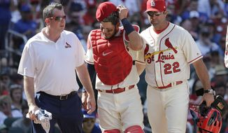 St. Louis Cardinals trainer Chris Conroy, left, and manager Mike Matheny (22) take catcher Yadier Molina back to the dugout after Molina was injured on a pitch during the ninth inning of a baseball game against the Chicago Cubs, Saturday, May 5, 2018, in St. Louis. (AP Photo/Charles Rex Arbogast)
