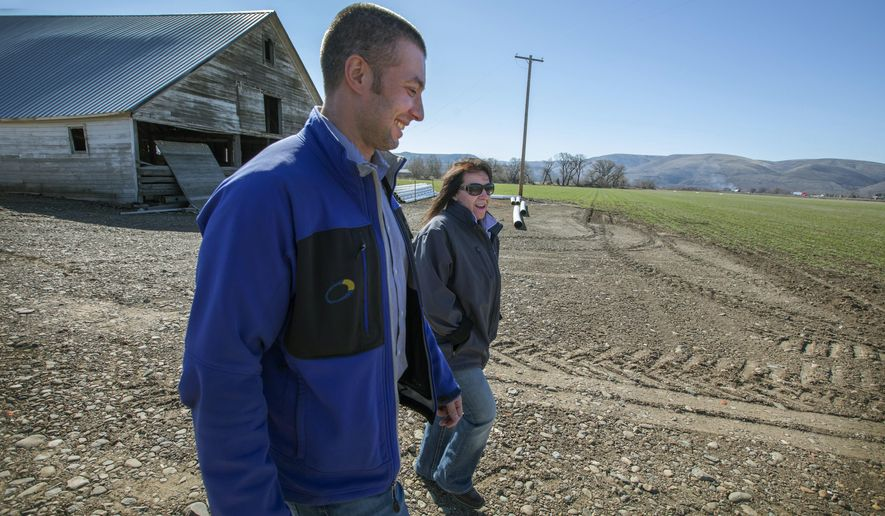 In this March 20, 2018 photo, farmer Jackie Brunson, right, walks with Tuusso Energy co-founder Jason Evans, whose project would place photovoltaic panels on some of the Brunson land and property belonging to three other Kittitas County landowners, in Ellensburg, Wash. (Steve Ringman /The Seattle Times via AP)