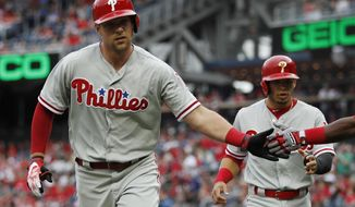 Philadelphia Phillies' Rhys Hoskins, left, celebrates after hitting a two-run home run in the first inning of a baseball game against the Washington Nationals at Nationals Park, Saturday, May 5, 2018, in Washington. Phillies Cesar Hernandez, right,  also scored on the play. (AP Photo/Carolyn Kaster)