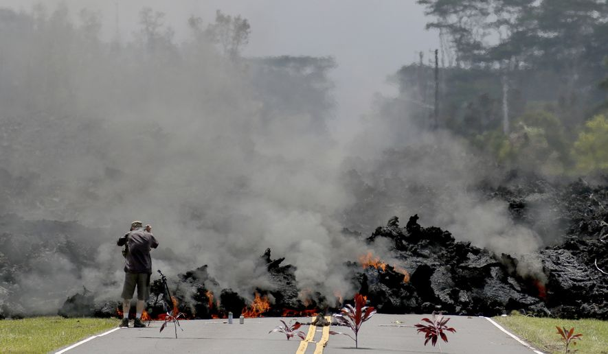 Lava burns across a road in the Leilani Estates subdivision as an unidentified person takes pictures of the flow, Saturday, May 5, 2018 near Pahoa, Hawaii. Offerings of Hawaiian ti leaves, rocks and cans to the fire goddess Pele lie in the street in front of the lava. (AP Photo/Caleb Jones)