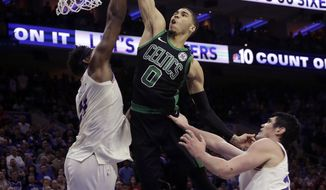 Boston Celtics' Jayson Tatum (0) goes up to shoot between Philadelphia 76ers' Joel Embiid, left, and Ersan Ilyasova, right, during the second half of Game 3 of an NBA basketball second-round playoff series, Saturday, May 5, 2018, in Philadelphia. (AP Photo/Matt Slocum)