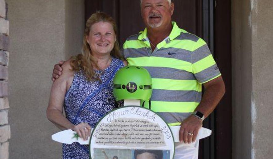 In this Wednesday, April 18, 2018, photo Ginger and Shaun Clark stand with a memorial for their son Shaun Clark in Indio, Calif. Since Shaun Jr.'s death, they have donated over 6000 green helmets. Shaun Clark was sitting on his front porch two days after his son was killed in a skateboarding accident when he saw a little boy on a scooter without a helmet. The grief-stricken Southern California father immediately ran and grabbed a helmet and shouted after the boy, begging him to put it on. The Desert Sun reports that Clark and his wife have distributed 6,000 bright green helmets to children in the region through the 4ShayJ Foundation. (Joseph Hong/The Desert Sun via AP)