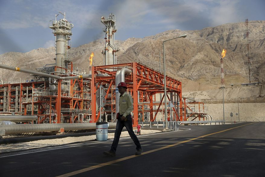 FILE - In this Nov. 19, 2015 file photo, a worker makes his way in a natural gas refinery in the South Pars gas field in Asalouyeh, Iran, on the northern coast of Persian Gulf. From brand-new airplanes to oilfields, billions of dollars of deals stand on the line for international corporations as President Donald Trump weighs whether to pull America out of Iran's nuclear deal with world powers. (AP Photo/Ebrahim Noroozi, File)