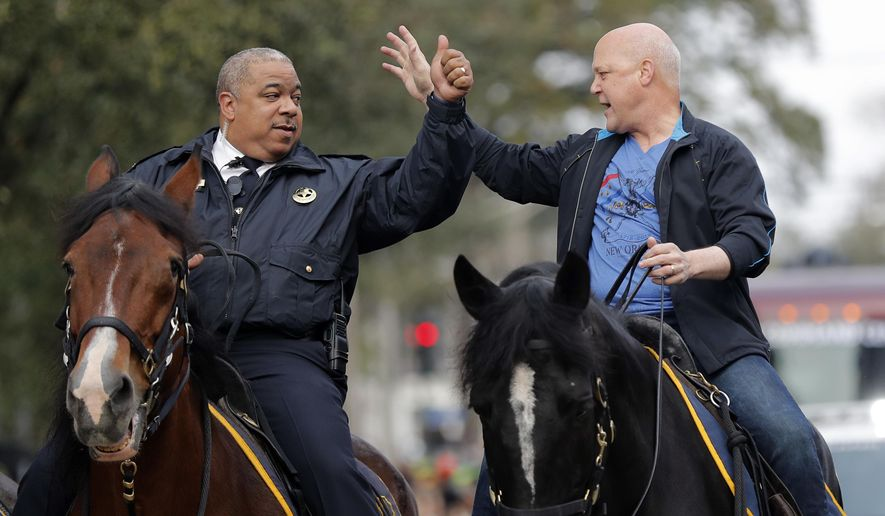 FILE - In this Feb. 13, 2018, file photo, New Orleans Mayor Mitch Landrieu, right, and chief of police Michael Harrison ride on horseback at the start of the Krewe of Zulu parade on Mardi Gras day in New Orleans. In many ways, Landrieu leaves the New Orleans mayor's office Monday, May 7, on high notes. But the term-limited Democrat leaves stubborn problems for his successor, LaToya Cantrell. They include an aging water, sewerage and drainage system and recurring violent crime. (AP Photo/Gerald Herbert, File)