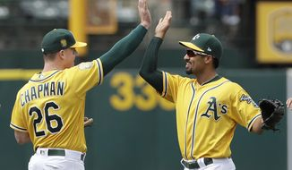 Oakland Athletics third baseman Matt Chapman, left, celebrates with shortstop Marcus Semien after defeating the Baltimore Orioles in a baseball game in Oakland, Calif., Sunday, May 6, 2018. (AP Photo/Jeff Chiu)