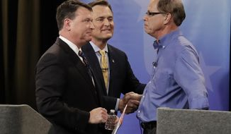 In this April 30, 2018, photo, Senate candidates from left, Todd Rokita, Luke Messer and Mike Braun speak with each other following the Indiana Republican senate primary debate in Indianapolis. As primary season kicks into high gear, Republicans are engaged in nomination fights that are pulling the party to the right, leaving some leaders worried their candidates will be out of a step with the broader electorate in the November election. (AP Photo/Darron Cummings, Pool)