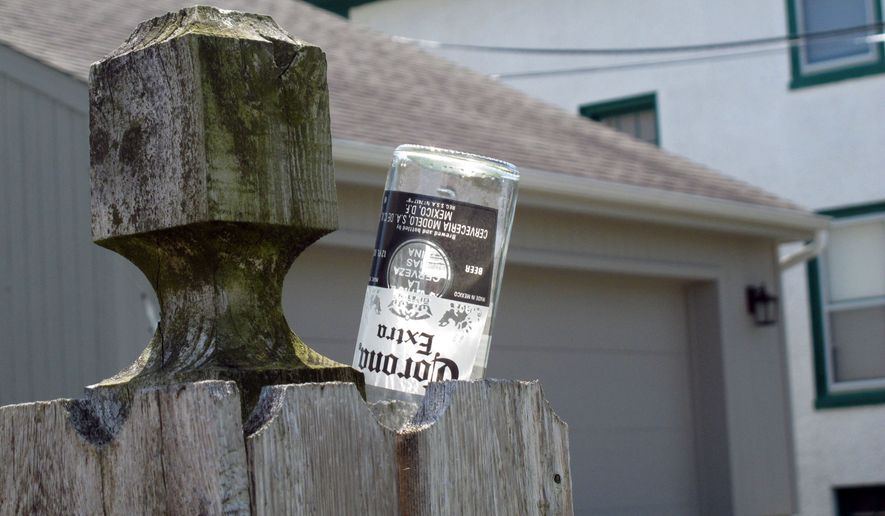 On May 6, 2012, the day after Cinco de Mayo celebrations, a beer bottle sits wedged into the fence of a homeowner near the Point Pleasant Beach, N.J. boardwalk. The town is taking a number of steps to combat what is sees as rowdy behavior by tourists drawn to boardwalk bars, including banning non-resident parking in areas nearest the bars from midnight to 6 am. It also might charge bars an extra fee to stay open past midnight, to help fund added police patrols. (AP Photo/Wayne Parry) **FILE**