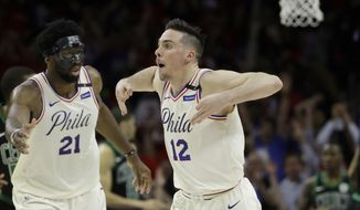 Philadelphia 76ers' T.J. McConnell (12) and Joel Embiid celebrate during the second half of Game 4 of an NBA basketball second-round playoff series against the Boston Celtics, Monday, May 7, 2018, in Philadelphia. Philadelphia won 103-92. (AP Photo/Matt Slocum)