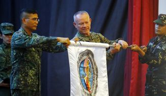 "Co-Exercise Directors Lt. Gen. Lawrence Nicholson, center, commander of the 3rd U.S. Marine Expeditionary Forces, and Northern Luzon commander Lt. Gen. Emmanuel Salamat, left, unfurl a flag of the joint U.S.-Philippines military exercise dubbed ""Balikatan 34-2018"" during the opening ceremony Monday, May 7, 2018 at Camp Aguinaldo in suburban Quezon city, northeast of Manila, Philippines. About 8,000 U.S. and Philippine troops are taking part in the annual exercise to enhance their interoperability in counterterrorism and Humanitarian Assistance and Disaster Response or HADR. Contingents from Australia and Japan are also taking part in the two-week exercise. (AP Photo/Bullit Marquez)"