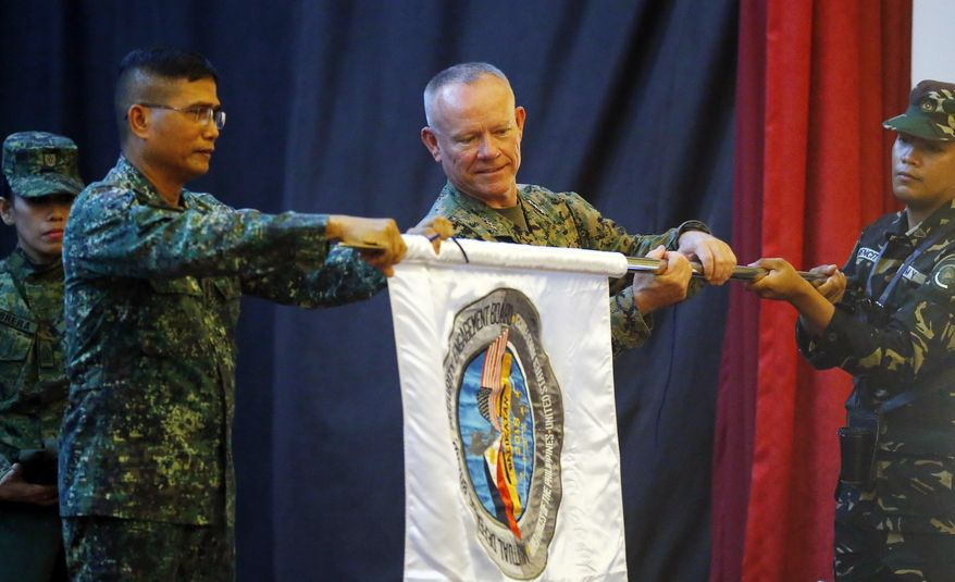 """Co-Exercise Directors Lt. Gen. Lawrence Nicholson, center, commander of the 3rd U.S. Marine Expeditionary Forces, and Northern Luzon commander Lt. Gen. Emmanuel Salamat, left, unfurl a flag of the joint U.S.-Philippines military exercise dubbed """"Balikatan 34-2018"""" during the opening ceremony Monday, May 7, 2018 at Camp Aguinaldo in suburban Quezon city, northeast of Manila, Philippines. About 8,000 U.S. and Philippine troops are taking part in the annual exercise to enhance their interoperability in counterterrorism and Humanitarian Assistance and Disaster Response or HADR. Contingents from Australia and Japan are also taking part in the two-week exercise. (AP Photo/Bullit Marquez)"""