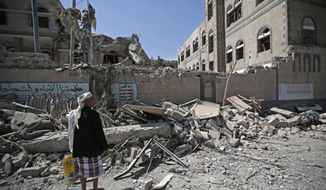 A man looks at damaged buildings after deadly airstrikes in and near the presidential compound, in Sanaa, Yemen, Monday, May. 7, 2018. Airstrikes by the Saudi-led coalition fighting Yemen's Shiite rebels targeted the presidency building in the heart of the Yemeni capital on Monday, leaving at least six people dead and some 30 wounded, according to health officials. (AP Photo/Hani Mohammed)