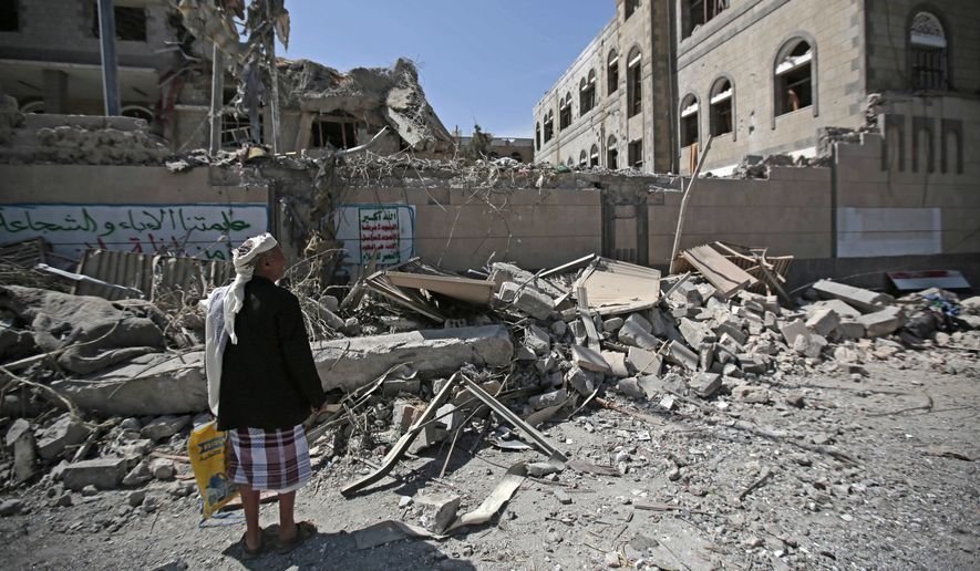 A man looks at damaged buildings after deadly airstrikes in and near the presidential compound, in Sanaa, Yemen, Monday, May. 7, 2018. Airstrikes by the Saudi-led coalition fighting Yemen's Shiite rebels targeted the presidency building in the heart of the Yemeni capital on Monday, leaving at least six people dead and some 30 wounded, according to health officials. (AP Photo/Hani Mohammed) ** FILE **