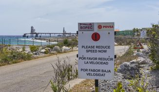 A warning sign stands at the entrance of the PDVSA/BOPEC Brasil Terminal in Rincon Bonaire on the Caribbean Netherlands island of Bonaire, Monday, May 7, 2018, where Venezuela refines and stores its heavy crude. U.S. oil giant ConocoPhillips is pressing for control of Venezuela's key offshore operations in the Caribbean, seeking to recoup $2 billion from a decade-old dispute with the nation struggling to feed its people, a source confirmed Monday. (AP Photo/Stephan Kogelman)