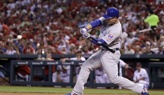 Chicago Cubs' Anthony Rizzo swings into a sacrifice fly off St. Louis Cardinals starting pitcher Michael Wacha during the first inning of a baseball game Sunday, May 6, 2018, in St. Louis. Willson Contreras scored on the play. (AP Photo/Charles Rex Arbogast)