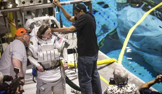 In a Thursday, April 12, 2018 photo, astronaut candidate Zena Cardman gets suited up for training in NASA's neutral buoyancy laboratory, in Houston. Space Center U is a challenging five-day program offered year-round to students so they can experience what training to be an astronaut might be like. (Brett Coomer/Houston Chronicle via AP)