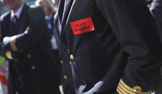 FILE - This Wednesday, April 11, 2018 file picture shows Air France pilots on strike as they gather next to the company headquarters during a demonstration in Tremblay-en-France, outside Paris, France. Sticker reads : Pilot on strike. Air France is grappling with a new strike, a sinking share price and a warning from the French government that the airline's survival is at stake. (AP Photo/Christophe Ena, File)