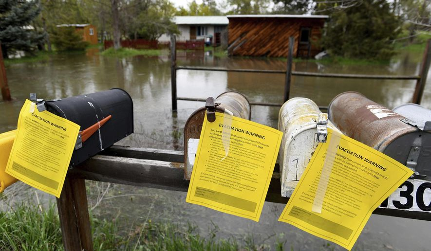 Evacuation warning notices hang on a row of mailboxes in front of a flooded area Monday, May 7, 2018, on the outskirts of Missoula, Mont. Sheriff's deputies in Montana went door to door Monday in a neighborhood along the rising Clark Fork River warning residents to prepare to leave, with the river expected to reach major flood levels in Missoula for the first time in 37 years.  (Kurt Wilson/The Missoulian via AP)