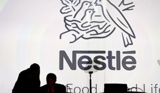 FILE - In this April 7, 2016, file photo Nestle's directors speak in front of the Nestle's logo during the general meeting of Nestle Group, in Lausanne, Switzerland. Nestle has entered an agreement to bring Starbucks products to millions of homes worldwide, announced Monday, May 7, 2018. (Laurent Gillieron/Keystone via AP, File)