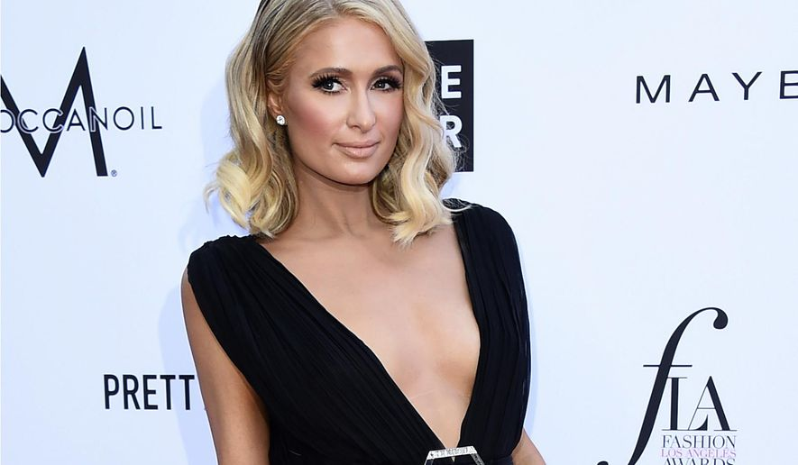 FILE - In this April 8, 2018 file photo, Paris Hilton arrives at the Daily Front Row's Fashion Los Angeles Awards in Beverly Hills, Calif. Hilton made an appearance in federal court to watch the sentencing of a woman who authorities say hacked her accounts to get bank and credit card information that she used to steal hundreds of thousands of dollars. (Photo by Jordan Strauss/Invision/AP, File)