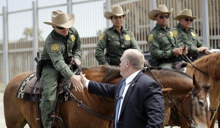 Immigration and Customs Enforcement Deputy Director Thomas Homan, front, shakes hands with mounted Border Patrol agents during a news conference along the border Monday, May 7, 2018, in San Diego. (AP Photo/Gregory Bull)